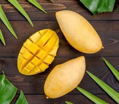 Mango fruit on green leaves, on wooden background.