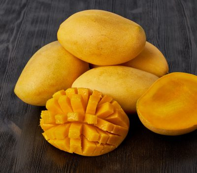 Four whole mango fruits on a wooden table and cut into slices. Large juicy bright ripe yellow fruits on a dark background, close up