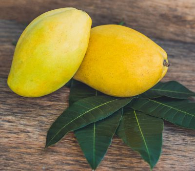 Mango and mango leaves on an old wooden background.